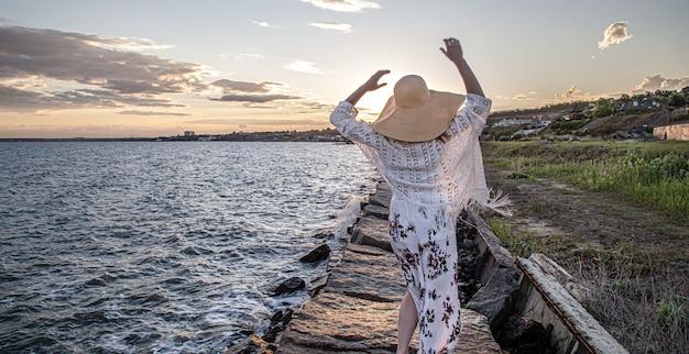 일몰 다시보기에서 바다로 여자입니다. 긴 치마와 모자를 입고.
