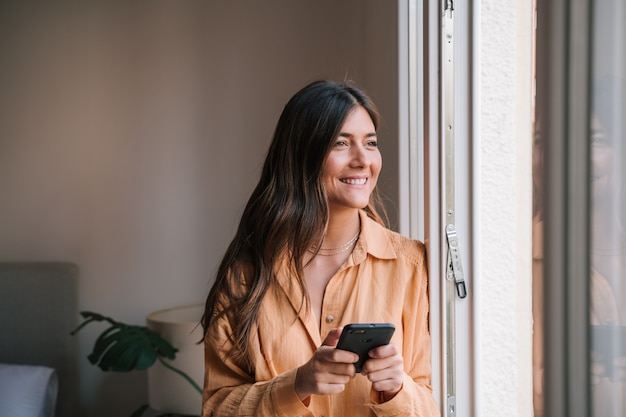 Woman by the window at home using mobile phone