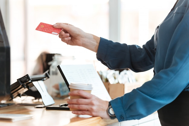 Woman in cafe holding credit card and coffee.