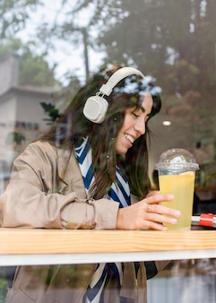 Woman in cafe with fresh lemonade and headphones