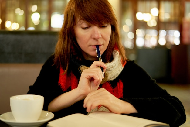 Woman in cafe writes in diary