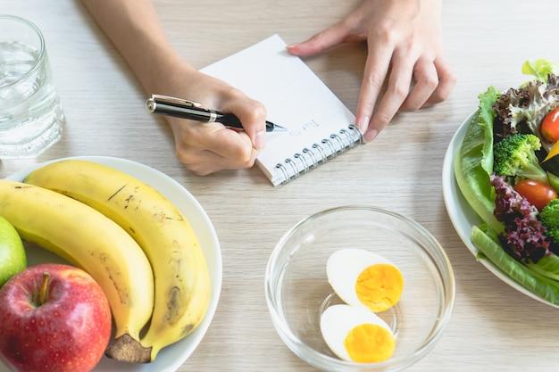 Женщина вычисляет калории пищи в завтрак во время диеты для программы похудения и t