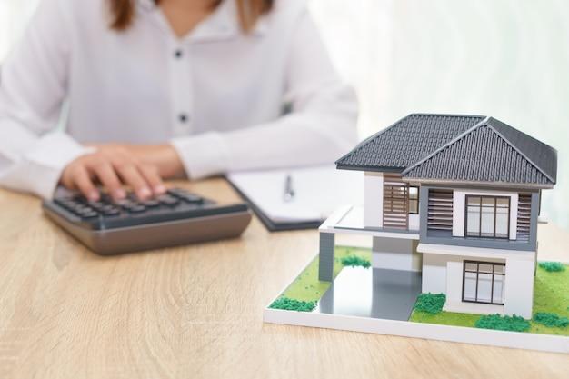 不動産ローン契約書で割賦価格を計算する女性
