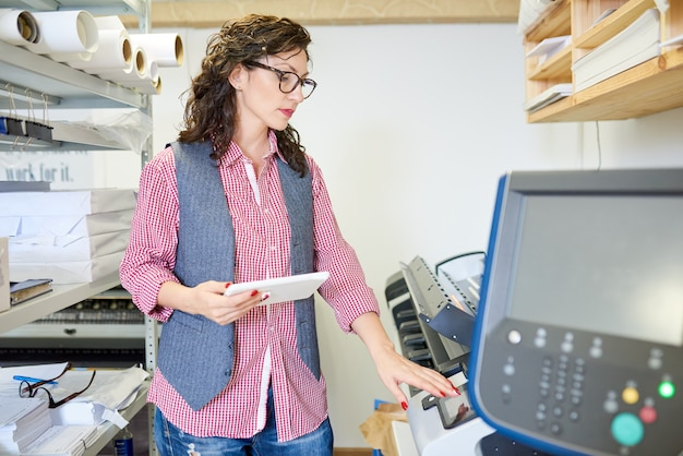 Woman calibrating printer in office