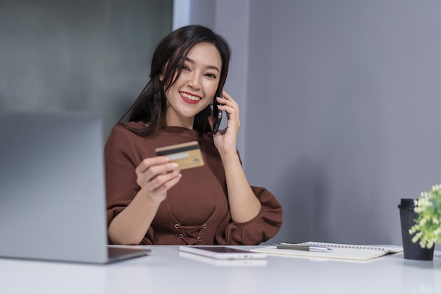 Woman calling by phone and holdind credit card to online shopping