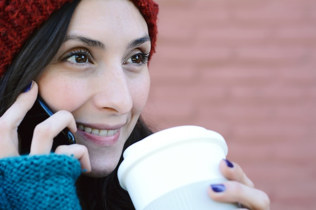 Woman calling on the mobile phone and holding a cup of coffee.