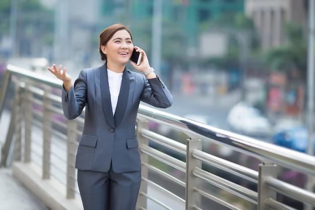 スマートフォンをかける女性と彼女は幸せを感じる