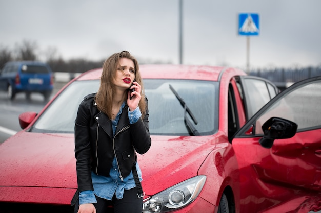 Woman calls to a service standing by a red car