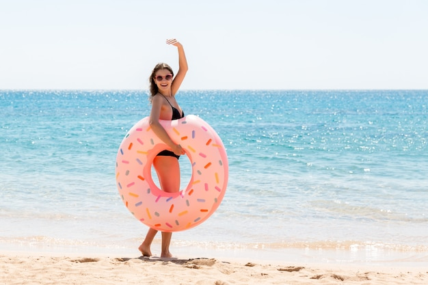 Woman calls to swim in the sea and waves her hand. girl relaxing with donut on the beach and playing with inflatable ring. summer holidays and vacation concept.