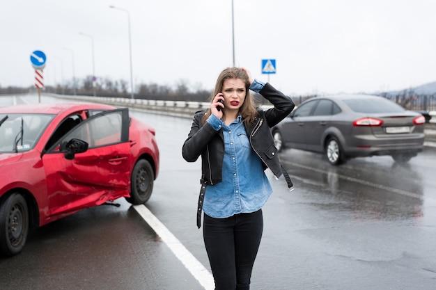 赤い車のそばに立っているサービスに女性が電話をかける