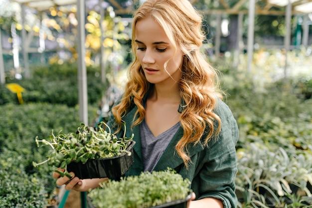 女性は家で自分で花を選ぶために植物店に来ました。物思いにふける女の子は選択に熱心です。