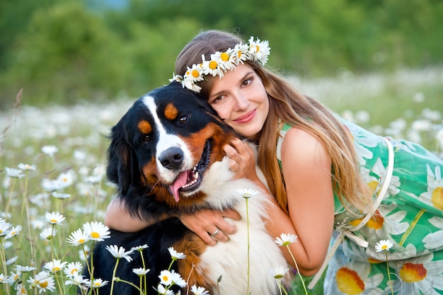 Woman in camomile wreath with bernese mountain dog. girl with dog