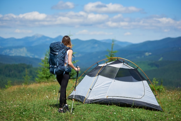 Woman camper near tent on the top of a hill against blue sky and clouds, looking away, resting after hiking, enjoying summer day in the mountains