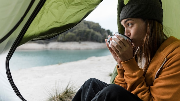 Woman camping and drinking tea sideways