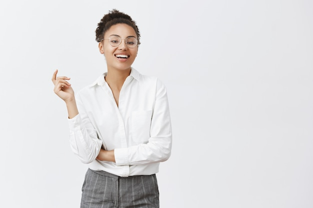 Woman can deal with any customer. attractive confident and feminine african woman with curly hair, gesturing with raised hand, smiling with self-assured expression, wearing suit and glasses