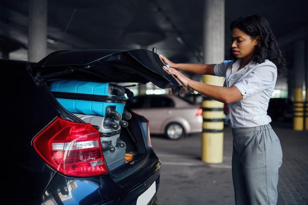 여자는 가방, 주차장으로 트렁크를 닫을 수 없습니다. 여성 여행자는 수하물, 차량 주차장, 많은 가방을 가진 승객을 포장합니다. 자동차 근처 수하물 소녀