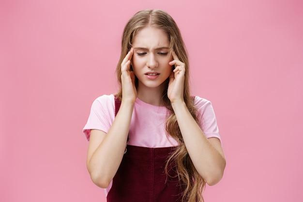 女性はテスト中に焦点を合わせることができず、心配そうに見下ろしている寺院に触れて答えが滑り落ち、頭痛やピンクの壁の上に立っている記憶の問題に悩まされていました。