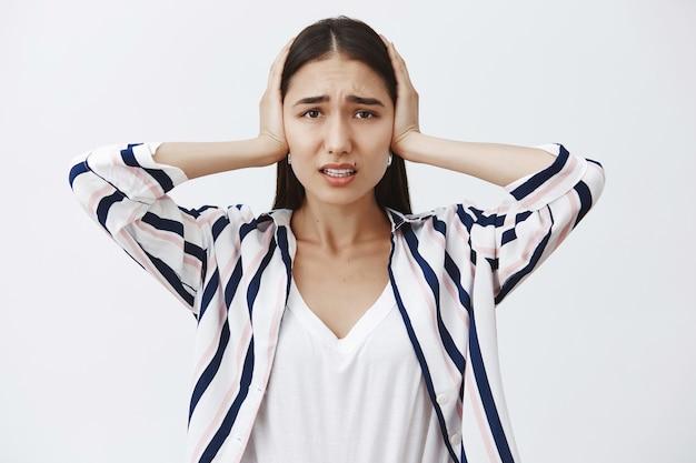 女性はもう圧力に対処できません。縞模様のブラウスに身を包んだ憂鬱な女性、耳を手のひらで覆い、眉をひそめ、悲しそうな表情で見つめ、大きな音から隔離する