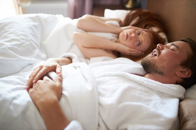 Woman cannot sleep while a man snores, she close ears and look at him