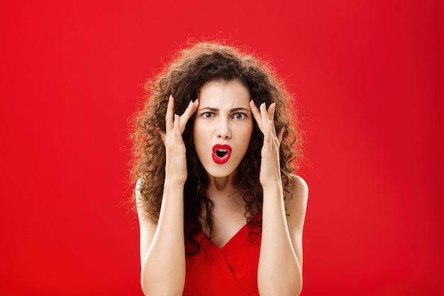 女性は愚かな人がどうあるべきか理解できません。彼女の周りの愚かな人々に不平を言っている寺院に指を持っている赤いドレスの巻き毛の髪型で腹を立ててイライラする不機嫌な怒っている女性。