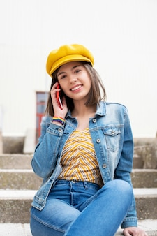 Woman in cap and denim jacket talking on the phone