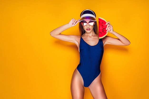 Woman in cap and swimwear holding slice of watermelon