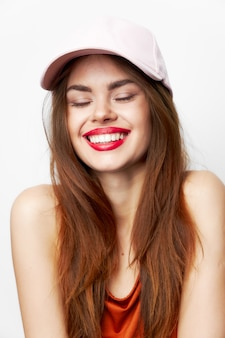 Woman in a cap wide smile closed eyes bare shoulders red dress isolated wall