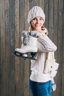 Woman in cap with skates behind back