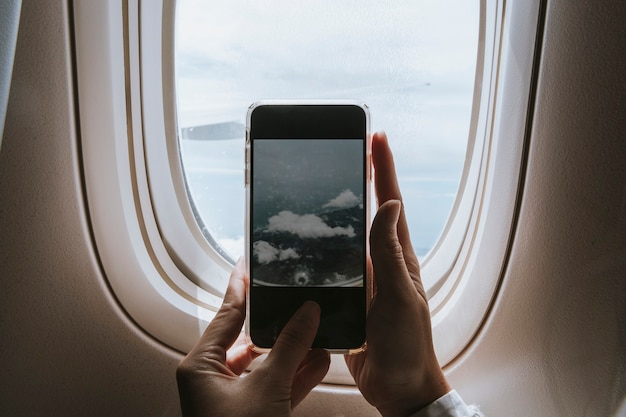 그녀의 전화로 비행기 창에서 구름을 캡처하는 여자