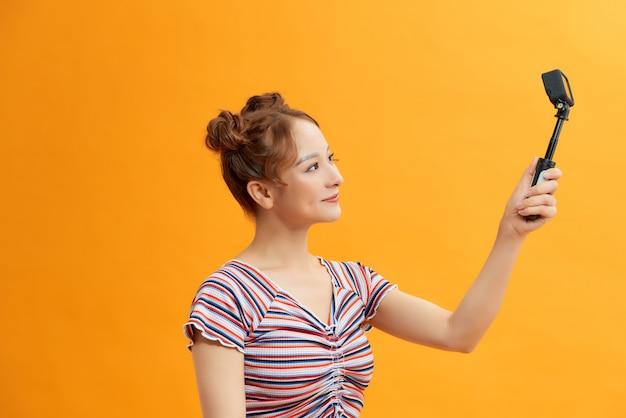 黄色の背景に小さなパーソナルカメラで自分自身をキャプチャする女性
