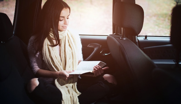 Woman in the car, autumn fall concept. smiling pretty girl reading a book moving in car