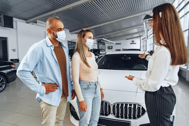 Woman car dealer consulting buyers wearing medical face shield. coronavirus job requirements concept