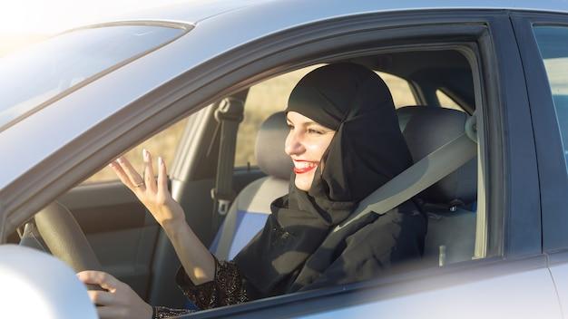 Водитель автомобиля женщина эмоционально машет руками. традиционная одежда