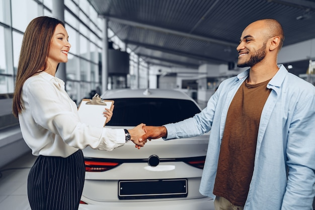 カーサロンの建物で握手する女性の車の売り手と男性の車の買い手