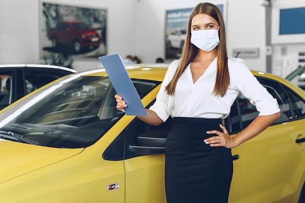 Женщина-продавец автомобилей, стоящая возле нового автомобиля в защитной маске в автосалоне