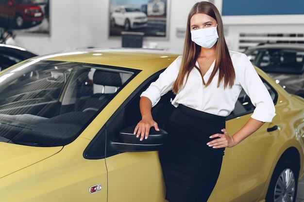 Женщина-продавец автомобилей стоит возле новой машины в защитной маске