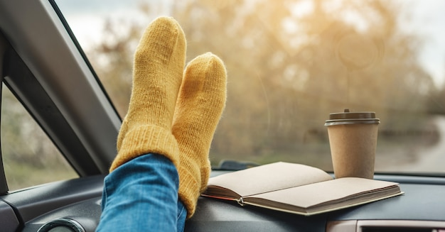 Woman in a car in warm woolen yellow socks on the car dashboard