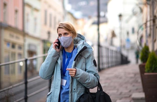 仕事に行く途中の屋外の女性介護者、看護師または医療従事者、コロナウイルスの概念。