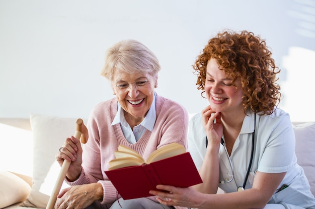 Woman caregiver reading a book while sitting with happy senior woman at nursing home.