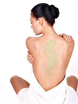 Женщина заботится о коже тела, используя косметический скраб на спине - изолированные на белом