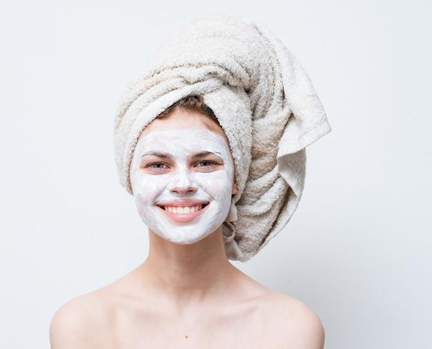 Женщина заботится о своей внешности, полотенце на голове и увлажняющий крем на лице.