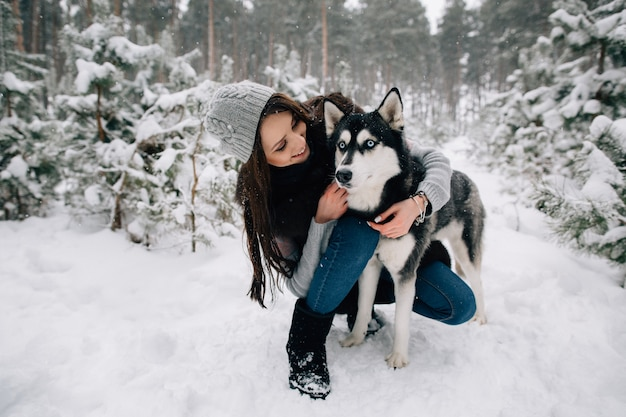 Woman caresses the husky dog in winter snowy cold day