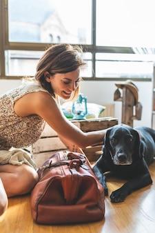 Женщина ласкает свою собаку дома