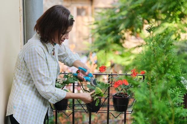 家の鉢植えの世話をする女性。花の近くの剪定はさみを持つ女性