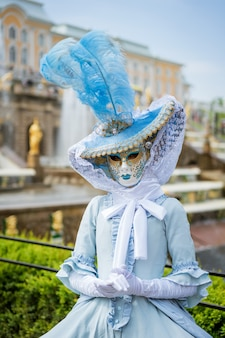 Woman in a carnival mask and in a blue dress against the background of fountains on a sunny day