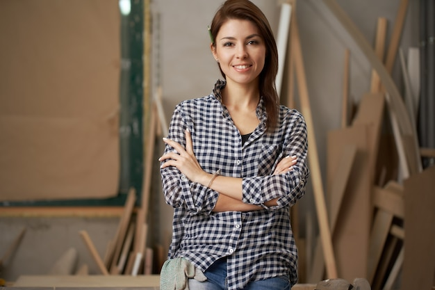 Woman carpenter in checkered shirt with arms crossed in workshop