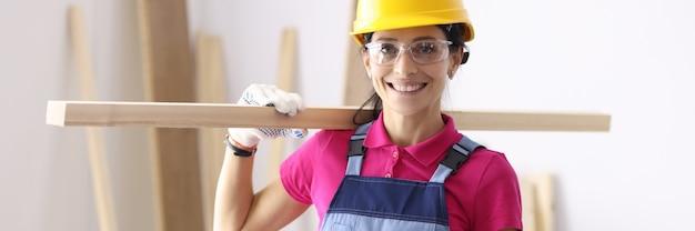 肩に木の板を保持している保護ヘルメットと眼鏡の女性大工。女性の概念のための大工の職業