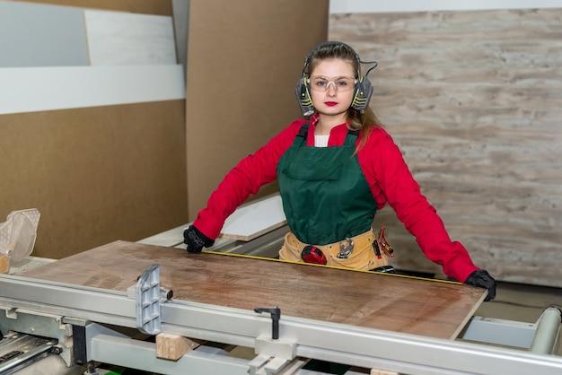 워크숍에서 여자 목수 측정 나무 판자
