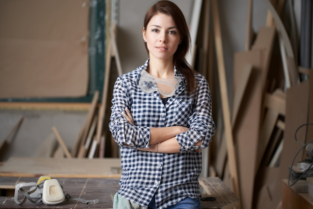 Woman carpenter with arms crossed in workshop