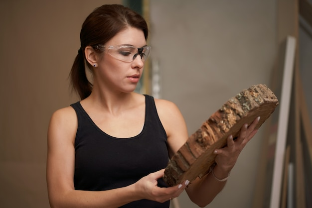 Woman carpenter with saw cut tree in hands in workshop